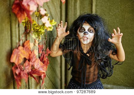 Cute child in wig and Halloween attire looking at camera with furious expression