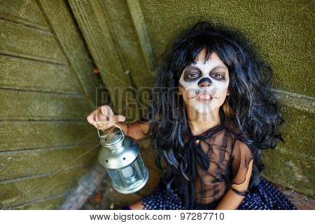Halloween girl in wig holding lantern and looking at camera with furious expression