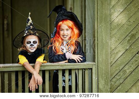 Little girls in Halloween attire standing by old house