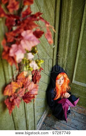 Little girl in Halloween attire sitting by wall of haunted house