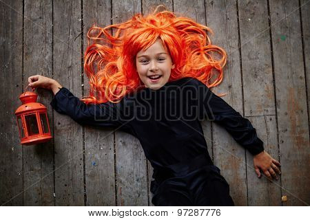 Cheerful little girl in orange wig and black attire looking at camera while lying on wooden floor