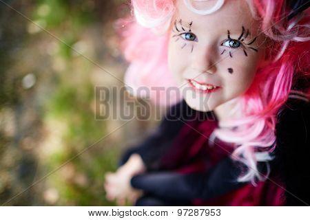 Smiling girl with pink wig and painted long eyelashes looking at camera