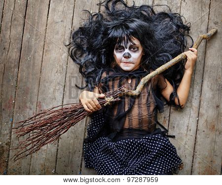 Little witch with broom looking at camera