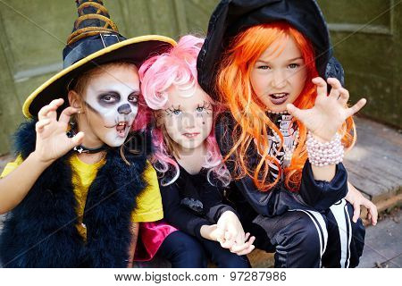 Group of frightening girls in Halloween costumes looking at camera