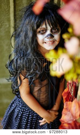 Happy Halloween girl in wig looking at camera with smile