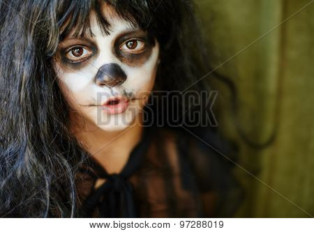 Little girl in wig with painted face looking at camera