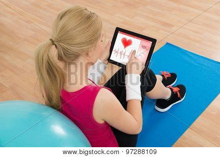 Woman Looking At Heart Pulse Rate On Digital Tablet