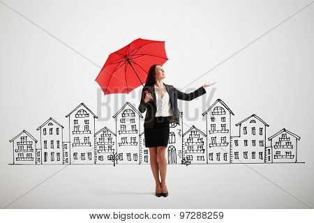 businesswoman with red umbrella held out her hand and looking up over grey background with drawing street