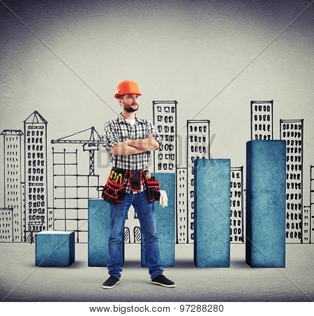 serious builder with folded hands over concrete diagram and drawing cityscape