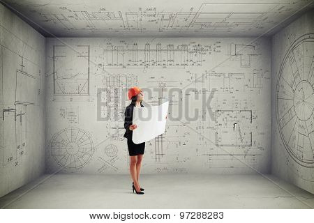 businesswoman in hardhat with blueprint looking up at prints on the walls and ceiling