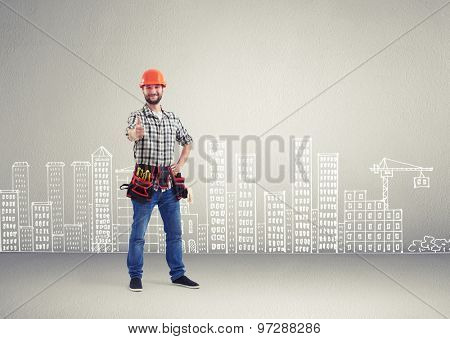 cheerful builder showing thumbs up and looking at camera over grey wall with drawing cityscape