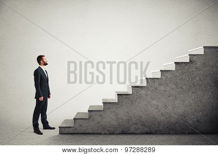 smiley businessman in formal wear standing near concrete stairs and looking at the top over light grey background