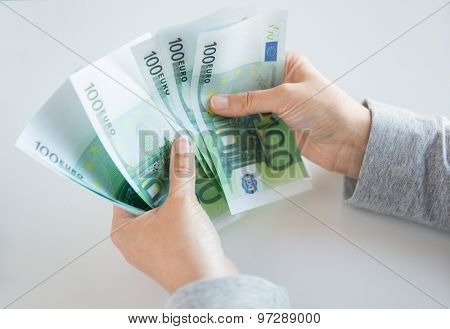 business, finance, saving, banking and people concept - close up of woman hands counting euro money