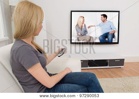 Woman With Remote Control In Front Of Television
