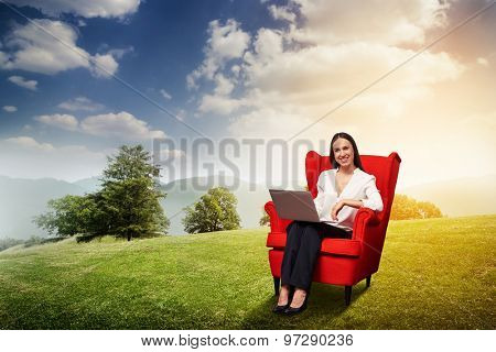 smiley businesswoman with laptop sitting on red chair and looking at camera over beautiful landscape