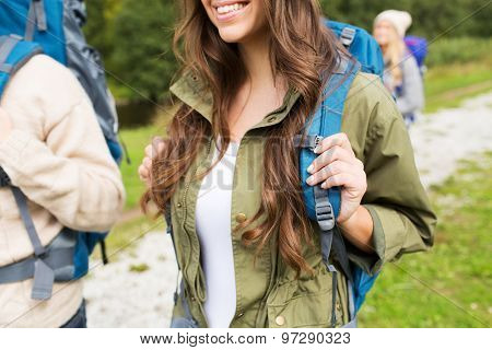 adventure, travel, tourism, hike and people concept - close up of happy woman and her friends hikers with backpacks walking on hiking trail