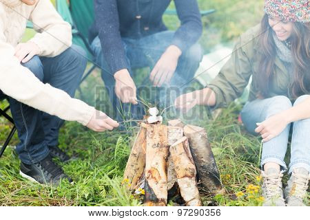 adventure, travel, tourism and people concept - close up of happy friends hikers roasting marshmallow on fire
