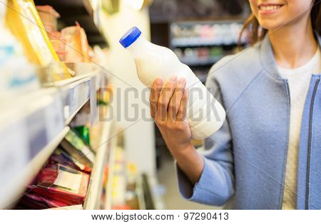 sale, shopping, consumerism, food and people concept - close up of happy young woman holding milk bottle in market