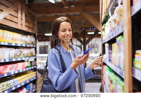 sale, shopping, consumerism and people concept - happy young woman with smartphone choosing and buying food in market
