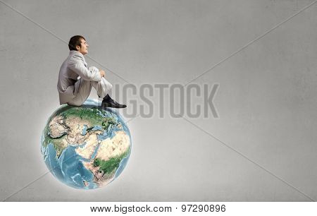 Young businessman sitting on Earth planet. Elements of this image are furnished by NASA