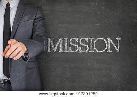 Mission on blackboard with businessman
