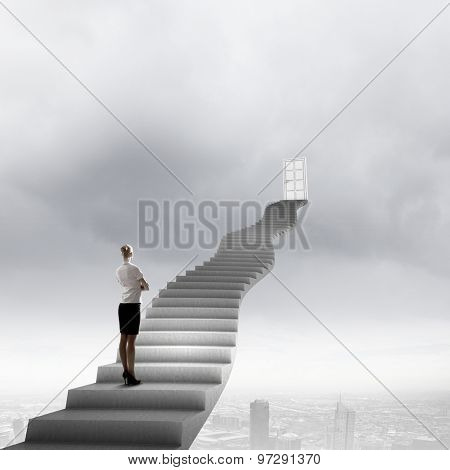 Businesswoman walking up staircase to door in sky