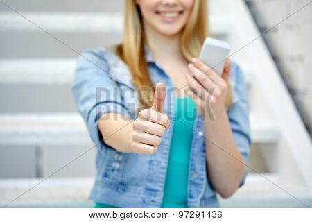 people, technology and internet concept - close up of happy teenage girl hands with smartphone showing thumbs up