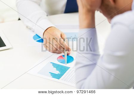 business, people, statistics and fail concept - close up of businessman hands showing chart to other anxious man man at office