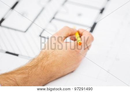 building, architecture, construction and people concept - close up of male hand with blueprint and pencil