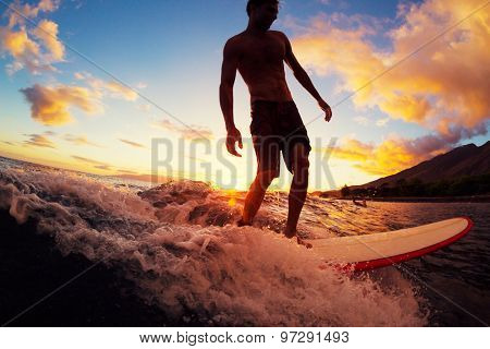 Surfing at Sunset. Young Man Riding Wave at Sunset. Outdoor Active Lifestyle.