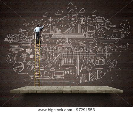 Back view of businessman standing on ladder and drawing sketch on wall
