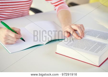 people and education concept - close up of female hands with book or textbook writing to notebook at school