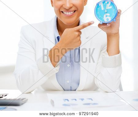 business, office, time, deadline concept - attractive businesswoman pointing at clock