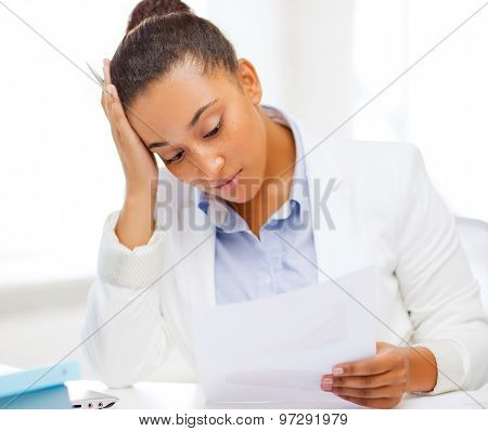 business and tax concept - african businesswoman working with calculator in office