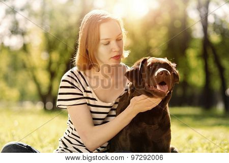 Young girl with retriever on walk in summer park
