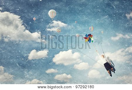 Beautiful young caucasian businesswoman flying on windmill