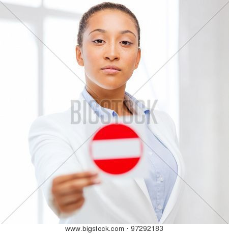 business, protest, racism concept - african woman showing stop sign