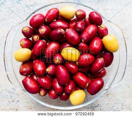 Freshly plucked date palm both red and yellow coloured ones kept in glass bowl on a plain background