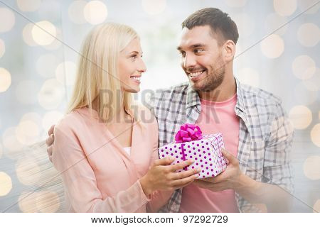 relationships, love, people, birthday and valentines day concept - happy man giving woman gift box over holidays lights background