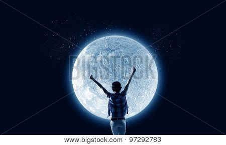 Rear view of young woman with hands up looking at moon in sky