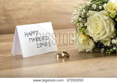 Close Up Of Beautiful Bride Bouquet Of  Fresh Flowers, Pair Of Rings And Happy Married Life Card