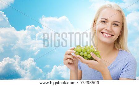 healthy eating, food, fruits, diet and people concept - happy woman eating grapes over blue sky and clouds background