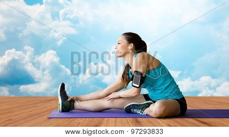 fitness, sport, training, technology and people concept - smiling woman with smartphone and earphones listening to music and stretching leg over wooden floor and sky with white clouds background