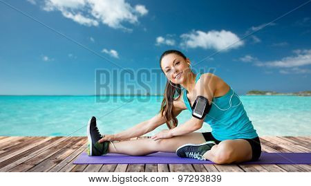fitness, sport, training, technology and people concept - smiling woman with smartphone and earphones listening to music and stretching leg over sea and wooden berth at resort background