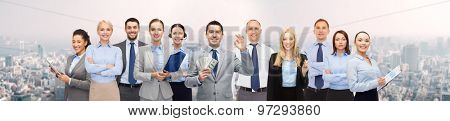 business, people, finances and banking concept - group of happy businesspeople with money bags over city background