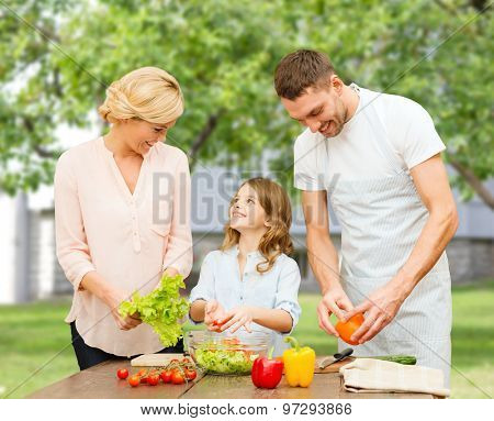 vegetarian food, culinary, happiness and people concept - happy family cooking vegetable salad for dinner over over summer house background