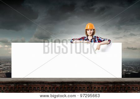 Young woman builder wearing helmet and holding blank banner
