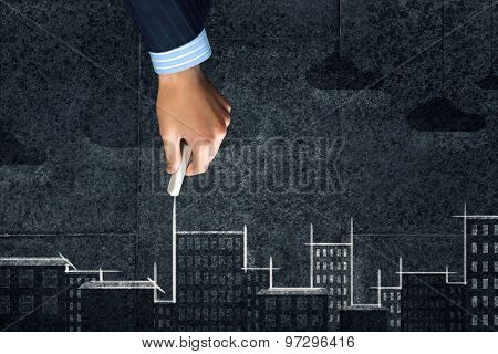 Close up of hand drawing urban city building on chalk board