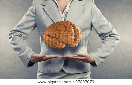 Businesswoman presenting in palms brain or save intelligence concept