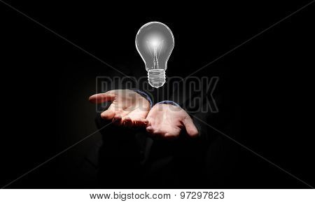 Close up of businessman holding symbol of  light bulb